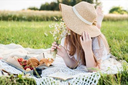 Summer day, picnic in the village. A beautiful girl in a hat lies on a plaid plaid. a bouquet of daisies, flowers in her hair.