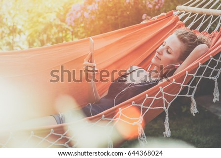 Summer day, young woman lying in orange hammock in park and listening to music on smartphone.Girl blogging, chatting, shopping online, using digital gadget.Lifestyle. Instagram filter. Social network. #644368024