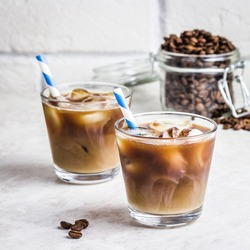 Summer drink iced coffee in glass and coffee beans in glass jar on white background. Selective focus, copy space.