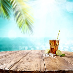 Summer drink on wooden table and free space for your decoration. Beach landcsape with sea and palms.