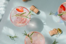 Summer drink with white sparkling wine. Homemade refreshing fruit cocktail or punch with champagne, strawberries, ice cubes and rosemary on light blue background.