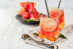 Summer drinks and cocktails. Lemonade, homemade sangria with fresh watermelon, lime, mint and pineapple. In two glasses,  on a white marble table. Copy space