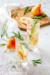 Summer drinks, rosemary pear cocktails with ice in glasses. Refreshing summer homemade Alcoholic or non-alcoholic cocktailsor Detox infused flavored water