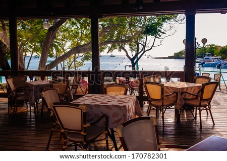 Summer empty open air restaurant near sea at sunset in Dominican Republic. Vintage black and white photography