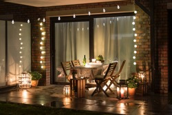 Summer evenig terrace with candles, wine and lights