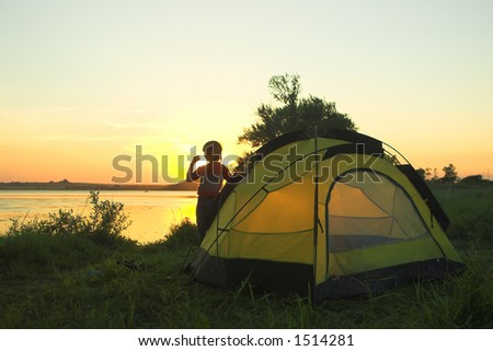 summer evening on the lake, boy with tent against sunset