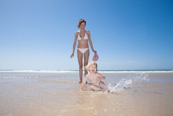 summer family of two years old blonde baby with blue swimsuit lying on ground and splashing water with brunette woman mother in white bikini at sea shore beach sand in Cadiz Andalusia Spain