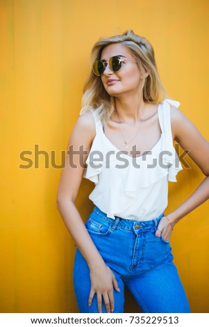 Summer, fashion and people concept - bright stylish portrait pretty woman in sunglasses against colorful wall in the city, street fashion