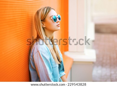 Summer, fashion and people concept - lifestyle portrait stylish pretty woman in sunglasses against colorful wall in city, street fashion