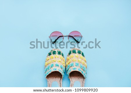 Summer fashion flatlay with gradient round sunglasses and espadrille sandals on the blue background. Perfect beach set for holidays on the sea. Marina style. #1099809920