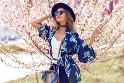 Summer fashion portrait of pretty   blonde woman posing  on amazing blooming tree background .Wearing sunglasses, casual hat , trendy blue silk kimono and  velvet choker.  Stylish  handbag.