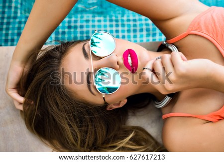 Summer fashion portrait of young beautiful model, lay near pool, bright lipstick, blue mirrored sunglasses, luxury lifestyle, enjoy vacation.