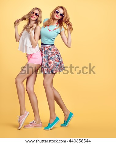 Summer.Fashion summer hipster woman, summer outfit having fun. Playful sisters friends crazy cheeky emotions. Girl in trendy summer sunglasses, summer wavy hairstyle posing, yellow.Unusual summer fun
