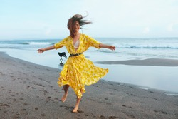 Summer Fashion. Woman In Bohemian Clothing Walking With Dog On Beach. Beautiful Model In Maxi Dress With Floral Pattern Enjoying Resting On Ocean Shore. Boho Style For Fashionable Look On Resort.
