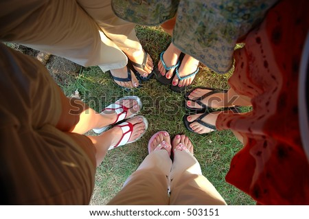 Summer Feet - A group of teen girlfriends stand in a huddle showing their painted toe nails and summer sandals.