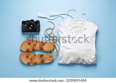 Summer festive background, beach female accessories white sundress, leather sandals and Camera on a blue background. Vacation and travel items. Top view Blue Background Flat Lay #1030895404
