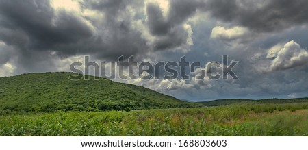 Summer field, mountains, forest and dramatic sky before a thunderstorm