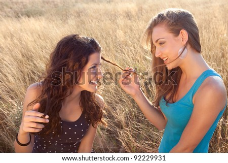 Summer field with two young girl friends in golden evening light