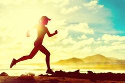 Summer fitness healthy active woman running on beach against sun flare at sunset. Runner athlete sport girl jogging on trail run race on nature landscape. Fit active lifestyle.