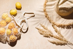 Summer flat lay on beige background. Straw hat and lemon fruits in eco friendly mesh shopping bag. Trendy palm shadow and sunlight, sun. Minimal summer travel fashion concept.