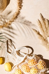 Summer flat lay on beige background. Straw hat and lemon fruits in eco friendly mesh shopping bag. Trendy palm shadow and sunlight, sun. Minimal summer travel fashion concept. Top view
