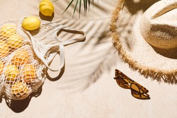 Summer flat lay on beige background. Straw hat, sunglasses, lemon fruits in eco friendly mesh shopping bag. Trendy palm shadow and sunlight, sun. Minimal summer travel fashion composition.