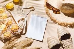 Summer flat lay on beige background. Straw hat, sunglasses, slippers and lemons in eco friendly mesh shopping bag. Palm shadow and sunlight, sun. Summer travel fashion concept.
