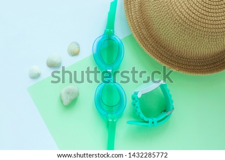 Summer flatlay with watersport goggles, staw hat, mint watch, seashells and stones, mint and light blue duotone background, minimalistic style, copy space. Sea rest, vacation with family. #1432285772