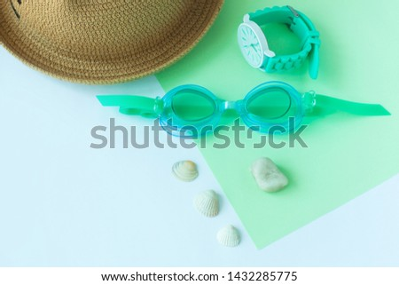 Summer flatlay with watersport goggles, staw hat, mint watch, seashells and stones, mint and light blue duotone background, minimalistic style, copy space. Sea rest, vacation with family. #1432285775