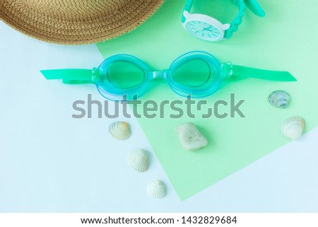Summer flatlay with watersport goggles, staw hat, mint watch, seashells and stones, mint and light blue duotone background, minimalistic geometric style, copy space. Sea rest, vacation with family. #1432829684
