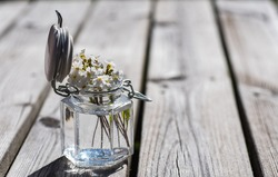 Summer flowers in a glass jar that is open on a wooden table outdoors and welcomes summer in Sweden