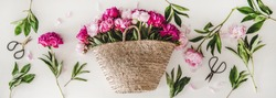Summer flowers layout. Flat-lay of pink and purple peony flowers in basket over plain white background, top view. Florist shop website banner or wallpaper