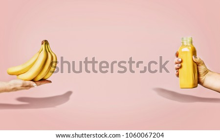 Summer food and beverages background with bananas and yellow drink bottle in female hand at pastel pink background, front view, banner or template.