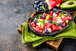 Summer food concept, fresh cold watermelon salad with feta cheese, blueberry, avocado and mint, dark rusty background copy space