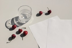 Summer food still life composition. Fresh red cherries fruit on beige table background. Stationery mock up scene. Blank paper pages. Glass of water, cocktail glittering in sunlight. Top view.