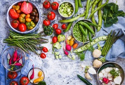 Summer food table with variety vegetables tomatoes, white and red radish, green peas and beans, pepper, spinach leaves, asparagus. Top view.