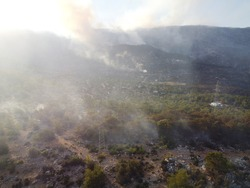 Summer forest fires. Smoke of a forest fire in the valley near Bogsak, Mersin province, Turkey. Natural disasters. Aerial view