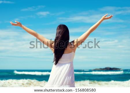 Summer freedom on the beach. Joyful woman raising arms to the sky, enjoying travel and vacation on coast. Playa de Verdicio, Asturias, Spain. - stock photo