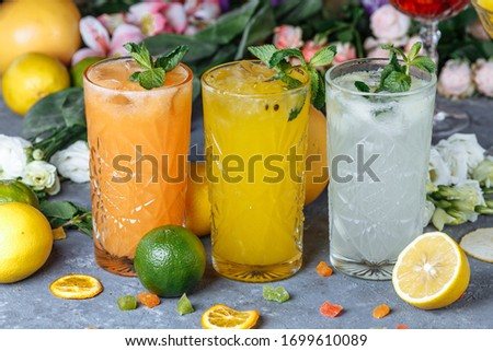 Summer fresh cold drink beverages. Ice Lemonade in the jug and lemons and orange with mint on the table outdoor. Orange lemonade in a glass.