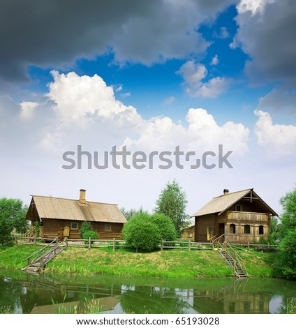 Summer from rural landscape. Wooden house near lake