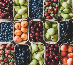 Summer fruit and berry assortment. Flat-lay of strawberries, cherries, grapes, blueberries, pears, apricots, figs in eco-friendly boxes over grey background, top view, close-up. Local farmers produce