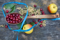 Summer fruit and tape measure. Red sour cherries, white currants and apples. Healthy vitamin food. Fitness diet.