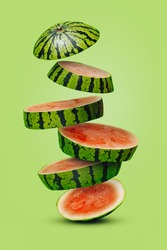 Summer fruit arrangement with slices of watermelon falling down stacked on a light green background. Creative food concept. Abstract composition.