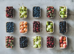 Summer fruit, berry assortment. Flat-lay of fresh strawberries, cherries, grape, blueberries, pears, apricots, figs in eco-friendly boxes over grey background, top view. Local farmers market produce
