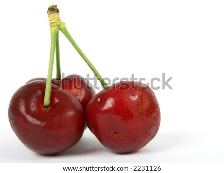 Summer fruit salad ingredients, healthy red cherries on green stalks, macro close up with copy space