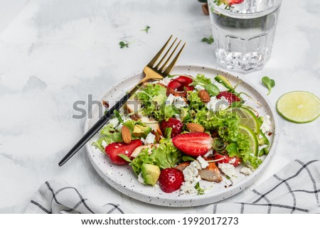 Summer fruit strawberry salad with chicken meat avocado, feta cheese, lettuce and nuts balsamic vinegar, concepts health food. Сток-фото ©