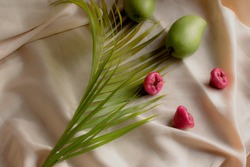 Summer fruits. Mango and Macopa (Mountain Apple). Green and pink fruits. Fruit photography, food styling. Fruits in elegant silk background. Fresh and nutritious. Food styling concept. Green mango.