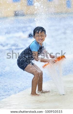 Summer fun at the water park. Boy playing  at swimming pool