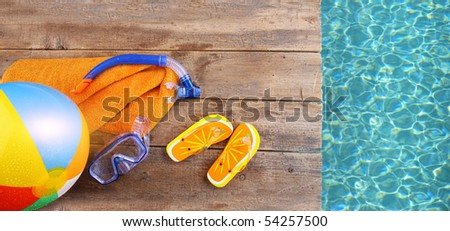 Summer fun background with flip flops, towel and goggles - stock photo
