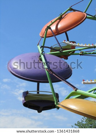 Summer fun. Close look at a section of a brightly colored carnival ride set against a bright blue sky with a few white clouds in the lower half of the vertical frame.  #1361431868